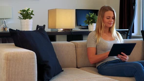 Thumbnail for Young Woman Sits on a Couch in a Living Room and Works on the Tablet