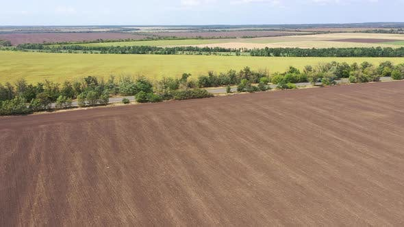 Thumbnail for Highway and agricultural fields aerial view, Trucks are moving along the highway