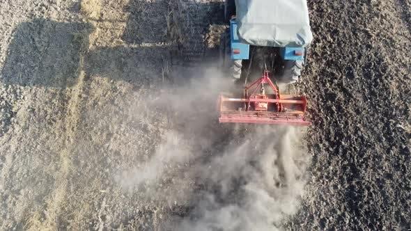 Landwirt benutzt Traktor, um den Müllcontainer zu räumen