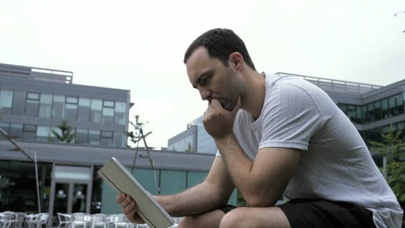 Thumbnail for Serious Casual Man Using Digital Tablet Sitting Outdoors.