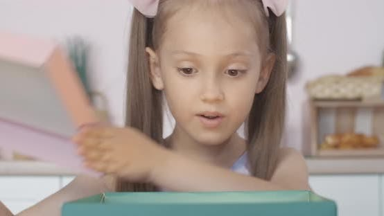Thumbnail for Nahaufnahme Gesicht des erstaunten kaukasischen Mädchens Eröffnung glühendes Geschenk und Blick nach innen. Porträt von Charme