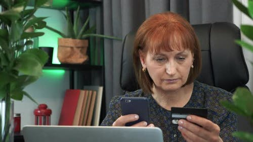 Businesswoman enters card number to smartphone for making online shopping