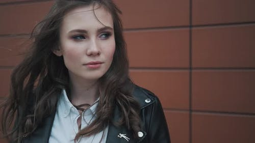 Hipster Girl in a Leather Jacket on the Background of Modern Architecture. Girl Looks and Smiles at