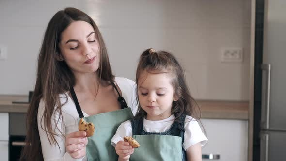 Thumbnail for Pretty Mother and a Daughter Are Eating Cookies in a Kitchen
