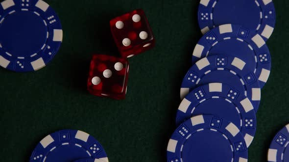 Rotating shot of poker cards and poker chips on a green felt surface - POKER 034