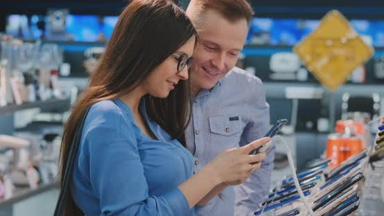 Thumbnail for Young Beautiful Couple. Man and Woman Hold in Hands a Smartphone Standing Near a Showcase