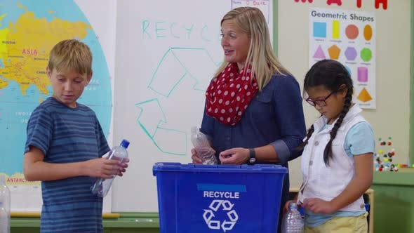Thumbnail for Teacher and students in school classroom putting bottles in recycle bin