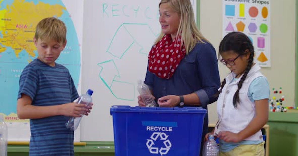 Teacher and students in school classroom putting bottles in recycle bin