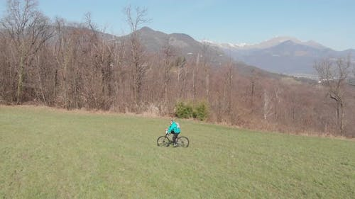 Aerial slow motion: man having fun by riding mountain bike in the grass on sunny day, scenic alpine
