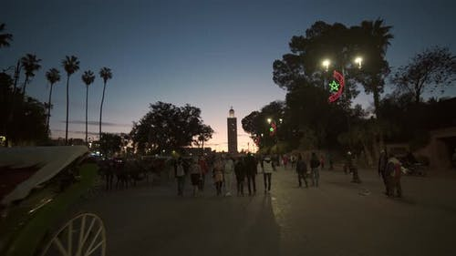 Tourists And Citizens Walking Through Marrakesh At Dusk