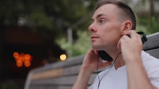 Man Listening to Music in Headphones Sitting on Bench