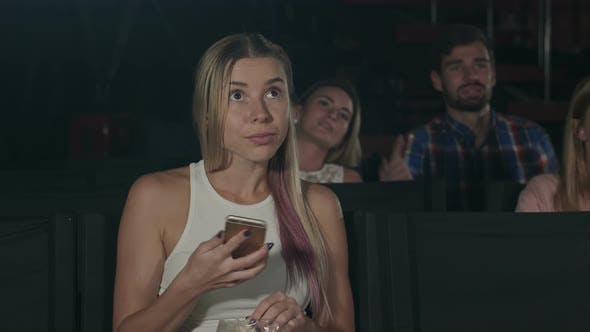 Thumbnail for Woman with Smartphone Reading Message in Movie Theater