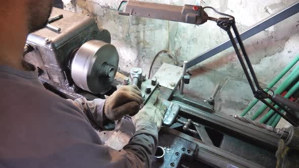 Thumbnail for Unrecognizable Man Working with Old Workbench in His Garage or Workshop. Mechanic Using Lathe for