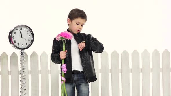 Thumbnail for Little Boy with Flowers Is Waiting for His Girlfriend, She Is Delayed. White Background. Slow Motion