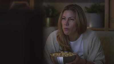 Woman Eating Popcorn and Watching Comedy