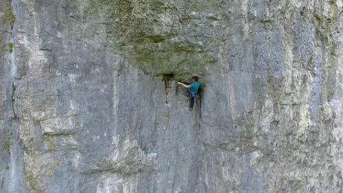 Aerial view of a man rock climbing up a mountain