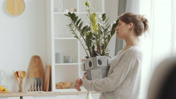 Thumbnail for Young Woman in Earphones Dancing with Houseplant at Home