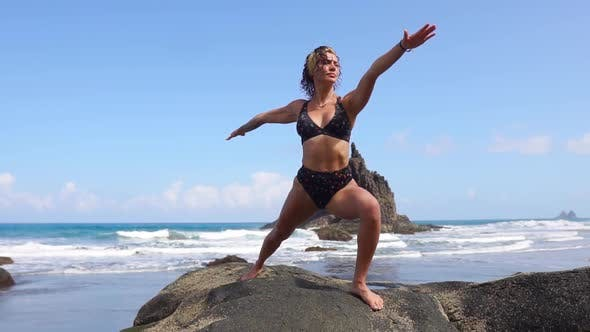 Thumbnail for Woman in Harmony with Nature Meditates Standing on a Stone on the Beach Near the Ocean