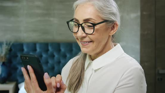 Thumbnail for Elderly Woman Texting on Smartphone