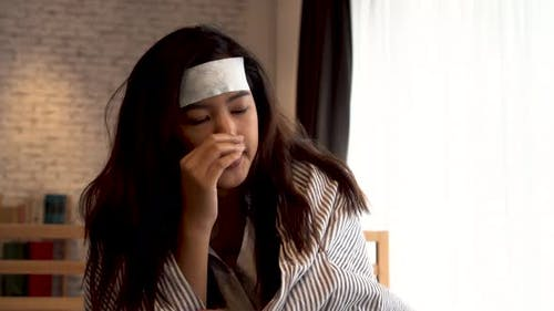 Young Asian Woman Suffering From Cold and Illness and Lying in Bed with Tissue at Home