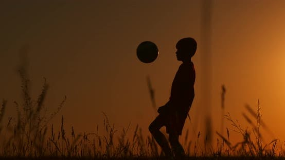 Thumbnail for Silhouette a Boy Juggles a Ball in the Field at Sunset.