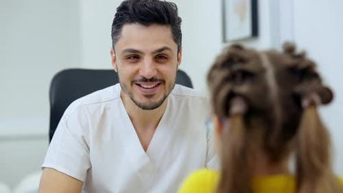 Portrait of Cheerful Handsome Middle Eastern Doctor Talking with Unrecognizable Girl Indoors