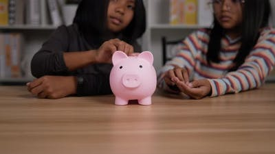 Two girls putting coins into piggy bank