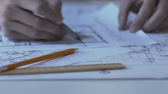 Cover Image for Architect checking building guidelines drawing, design bureau, hands closeup