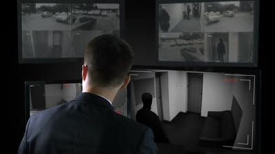 Security Guard in Front CCTV Footage Watching Bank Robbery, Calling Police