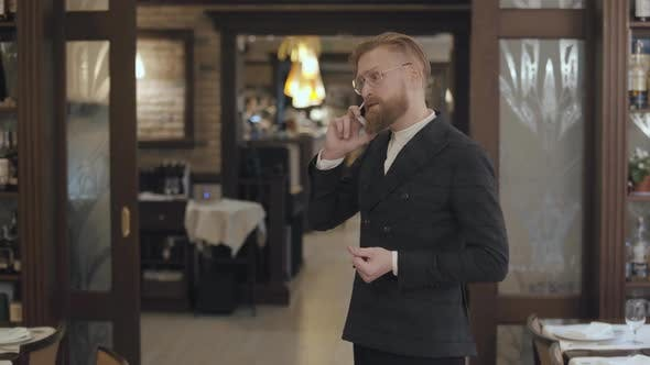 Thumbnail for Portrait of a Successful Business Man in Stylish Glasses with a Red Beard Talking