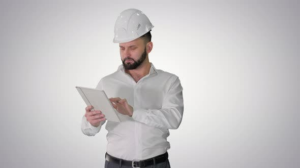 Construction Specialist Using a Tablet Computer While Walking on Gradient Background.