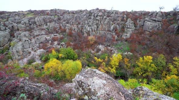 Aktovsky Canyon in der Ukraine, umgeben von Herbstbäumen und großen Steinbrocken