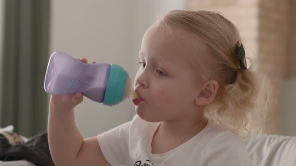 Kleines Kind trinkt Milch aus der Flasche