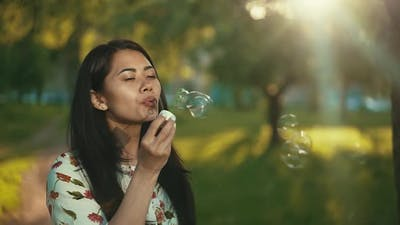 Asian Woman Blowing Soap Bubbles at the Sunset