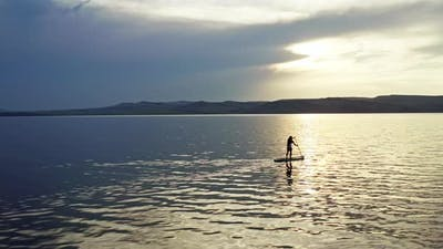 Drone Shot of a Woman with Long Hair Surfing on a Mountain Lake at Sunset