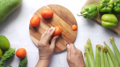 Hand Of Person Cutting Tomatoes On Chopping Board