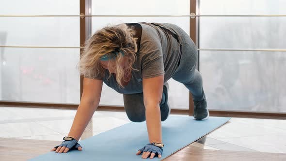 Thumbnail for Overweight Woman Doing Exercise on Mat in a Gym
