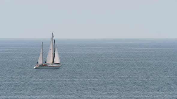 Yacht with sails in quiet blue sea