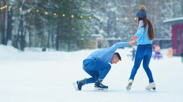 Thumbnail for Girl Helps Boyfriend Stand Up From Ice on Skating Rink