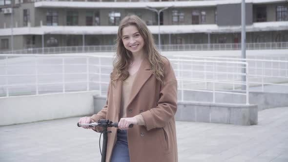 Thumbnail for Portrait of Smiling Beautiful Girl Posing with Scooter Outdoors on Cloudy Day. Middle Shot of