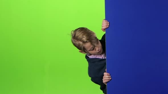 Thumbnail for Teen Peeks Out From the Side the Boards and Shows Dislike on a Green Screen. Slow Motion