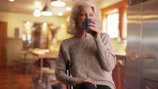 Thumbnail for Lovely elder woman drinking coffee inside kitchen turning to smile at camera