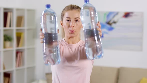Thumbnail for Woman Doing Exercise with Water Bottles and Looking at Camera