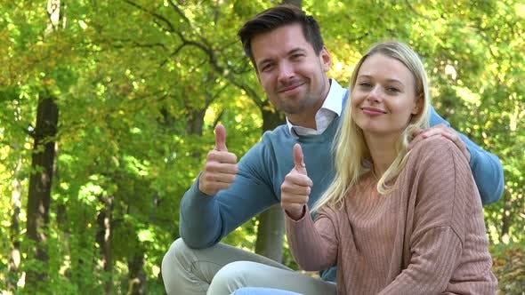 Thumbnail for A Young Couple Sits in a Park on a Sunny Day and Shows a Thumb Up To the Camera with a Smile