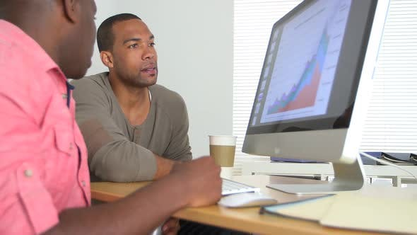 Thumbnail for Two Black Business men looking at sales data