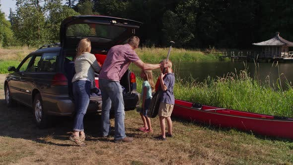Family unloading car at camp site