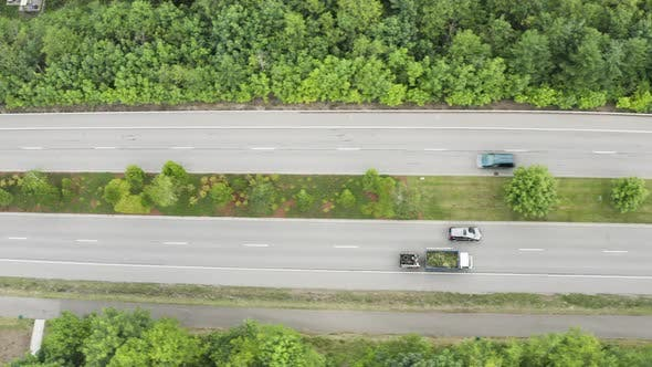 Cover Image for Landscaping Truck With Trailer Traveling On Road Filled With Yard Waste Aerial View From Above