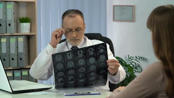 Thumbnail for Neurosurgeon Analyzing Brain X-Ray and Talking to Patient About Serious Illness