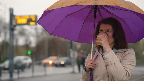 Woman with Umbrella Drinking Coffee in the City