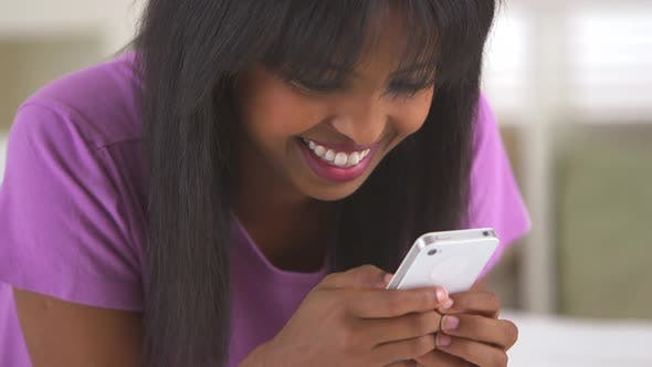 Thumbnail for African American girl texting on mobile phone